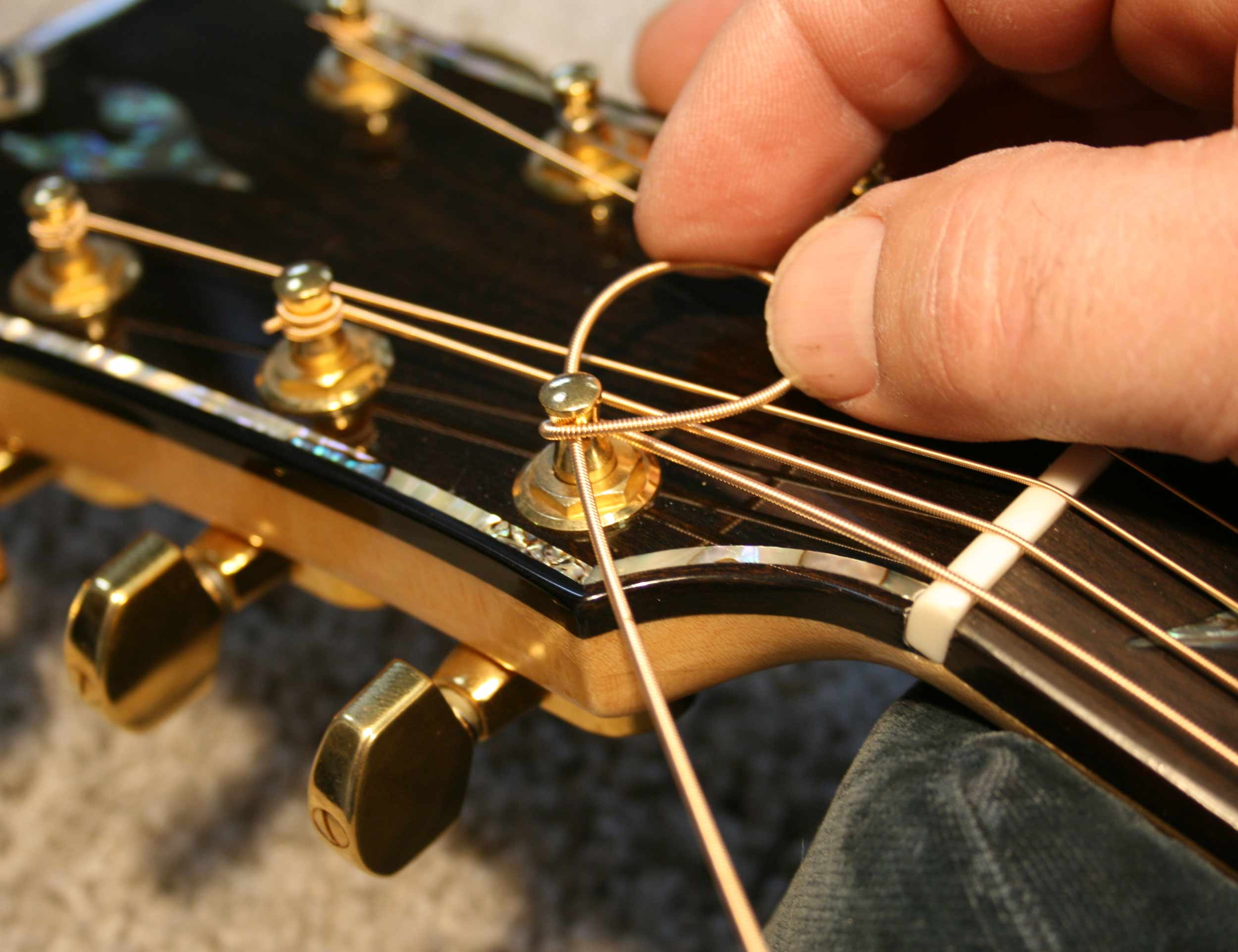 how to hold guitar strings